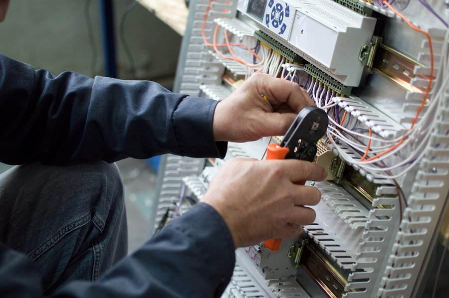 Electrician assembling industrial control cubicle in workshop. Close-up photo.