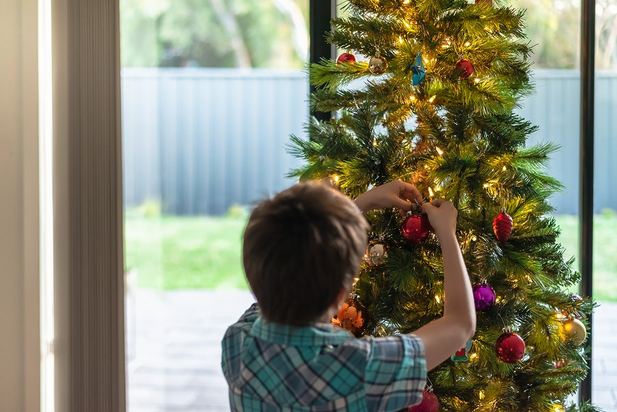 Boy decorating a Christmas tree, South Australia. Focus on hands